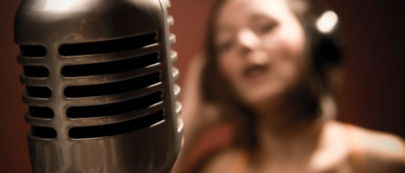 Shallowly Focused Young Woman Singing into Microphone